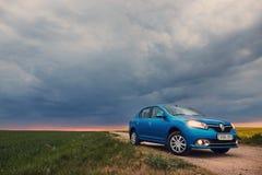 GOMEL, BIELORRÚSSIA - 15 de maio de 2018: O carro azul de RENO LOGAN estacionou no campo contra um céu tormentoso imagens de stock royalty free