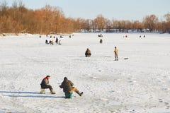 GOMEL, Bielorrússia - 24 de março de 2018: Pesca do inverno Pescadores nos peixes da captura do gelo Fotos de Stock