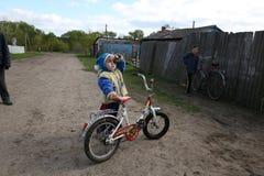 Gomel, Bielorrusia - 27 de abril de 2016: la vida de niños bielorrusos en el pueblo Derbichi cycling 27 de abril de 2016 en el pu imagen de archivo libre de regalías