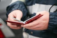 GOMEL, BIELORRUSIA - 18 de diciembre de 2017: Un oficial de patrulla del camino comprueba documentos del conductor imagen de archivo libre de regalías