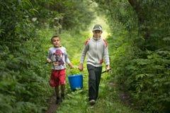 GOMEL, BIELORRUSIA - 25 de junio de 2017: Los niños del pueblo van a pescar con un cubo y las cañas de pescar Fotografía de archivo libre de regalías