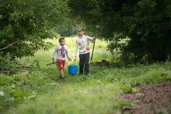GOMEL, BIELORRUSIA - 25 de junio de 2017: Los niños del pueblo van a pescar con un cubo y las cañas de pescar Foto de archivo libre de regalías
