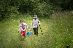 GOMEL, BIELORRUSIA - 25 de junio de 2017: Los niños del pueblo van a pescar con un cubo y las cañas de pescar Imagen de archivo