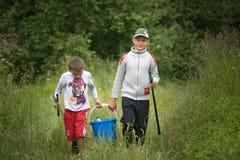 GOMEL, BIELORRUSIA - 25 de junio de 2017: Los niños del pueblo van a pescar con un cubo y las cañas de pescar Fotografía de archivo