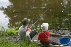 GOMEL, BIELORRUSIA - 25 de junio de 2017: Niños del pueblo que pescan en el lago con las cañas de pescar Imagen de archivo libre de regalías