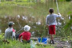 GOMEL, BIELORRUSIA - 25 de junio de 2017: Niños del pueblo que pescan en el lago con las cañas de pescar imágenes de archivo libres de regalías