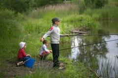 GOMEL, BIELORRUSIA - 25 de junio de 2017: Niños del pueblo que pescan en el lago con las cañas de pescar Fotografía de archivo libre de regalías