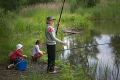 GOMEL, BIELORRUSIA - 25 de junio de 2017: Niños del pueblo que pescan en el lago con las cañas de pescar fotografía de archivo