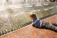GOMEL, BIELORRUSIA - 14 de mayo de 2017: Juego de niños con agua cerca de una fuente de la ciudad en la ciudad de Gomel Fotos de archivo libres de regalías