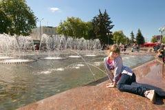 GOMEL, BIELORRUSIA - 14 de mayo de 2017: Juego de niños con agua cerca de una fuente de la ciudad en la ciudad de Gomel Foto de archivo