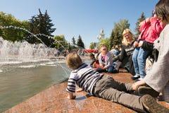 GOMEL, BIELORRUSIA - 14 de mayo de 2017: Juego de niños con agua cerca de una fuente de la ciudad en la ciudad de Gomel Foto de archivo libre de regalías