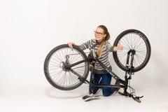 GOMEL, BIELORRUSIA - 12 de mayo de 2017: PISTA de la bici de montaña en un fondo blanco La muchacha está montando Imágenes de archivo libres de regalías