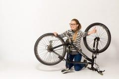 GOMEL, BIELORRUSIA - 12 de mayo de 2017: PISTA de la bici de montaña en un fondo blanco La muchacha está montando Foto de archivo libre de regalías