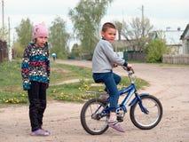 GOMEL, BIELORRUSIA - 4 DE MAYO DE 2019: Los niños montan una bici en el pueblo de Derbichi imagen de archivo