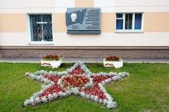 Gomel, Bielorrusia, el 12 de agosto de 2009: La visión en la casa con una placa conmemorativa y un macizo de flores en la calle E imágenes de archivo libres de regalías