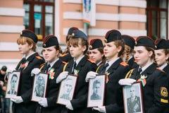 Gomel, Bielorrusia Formación que marcha de muchachas del cadete de la escuela del cadete del estado de Gomel con los retratos Fotos de archivo libres de regalías