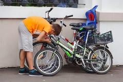 GOMEL VITRYSSLAND - Juli 25, 2018: en tonåring som parkerar 3 cyklar arkivfoto