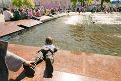 GOMEL VITRYSSLAND - Maj 14, 2017: Barnlek med vatten nära en stadsspringbrunn i staden av Gomel Arkivfoto