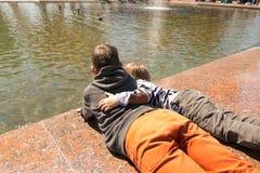 GOMEL VITRYSSLAND - Maj 14, 2017: Barnlek med vatten nära en stadsspringbrunn i staden av Gomel Arkivbild