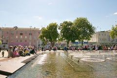 GOMEL VITRYSSLAND - Maj 14, 2017: Barnlek med vatten nära en stadsspringbrunn i staden av Gomel Arkivbilder