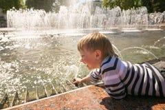 GOMEL VITRYSSLAND - Maj 14, 2017: Barnlek med vatten nära en stadsspringbrunn i staden av Gomel Royaltyfri Foto