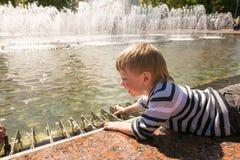 GOMEL VITRYSSLAND - Maj 14, 2017: Barnlek med vatten nära en stadsspringbrunn i staden av Gomel Royaltyfri Fotografi