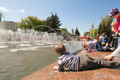 GOMEL VITRYSSLAND - Maj 14, 2017: Barnlek med vatten nära en stadsspringbrunn i staden av Gomel Royaltyfri Bild