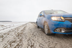 Gomel, Weißrussland - 21. Februar 2017: Auto Renault - Logan im Winterwald mit Scheinwerfern Lizenzfreies Stockbild