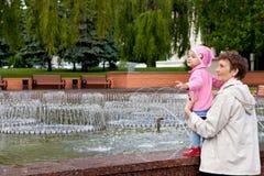 Gomel, Weißrussland, am 18. Mai 2010: Die Großmutter und die Enkelin sprechen am Brunnen auf der Straße Sovetskaya Stockbild