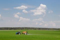Gomel, Weißrussland - 4. Mai 2016: Traktorsprühweizenfeld mit Sprüher, Herbiziden und Schädlingsbekämpfungsmitteln lizenzfreie stockbilder