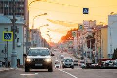 Gomel, Weißrussland Verkehr auf Lenin-Allee auf gelbem Sonnenuntergang mit dem Bewegen Stockfotografie