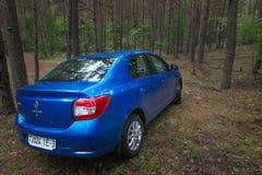 GOMEL, WEISSRUSSLAND - 24. MAI 2017: Blaues Auto RENO LOGANs parkte in einem dunklen Kiefernwald Lizenzfreie Stockfotos