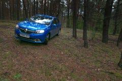 GOMEL, WEISSRUSSLAND - 24. MAI 2017: Blaues Auto RENO LOGANs parkte in einem dunklen Kiefernwald Lizenzfreie Stockfotografie