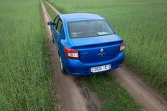 GOMEL, WEISSRUSSLAND - 24. Mai 2017: Blaues Auto RENO LOGANs wird auf dem grünen Feld geparkt Lizenzfreies Stockfoto