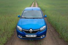 GOMEL, WEISSRUSSLAND - 24. Mai 2017: Blaues Auto RENO LOGANs wird auf dem grünen Feld geparkt Stockbilder