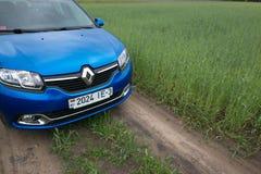 GOMEL, WEISSRUSSLAND - 24. Mai 2017: Blaues Auto RENO LOGANs wird auf dem grünen Feld geparkt Stockfotografie