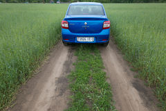 GOMEL, WEISSRUSSLAND - 24. Mai 2017: Blaues Auto RENO LOGANs wird auf dem grünen Feld geparkt Stockfoto