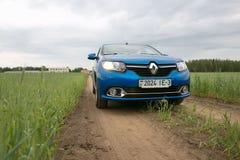 GOMEL, WEISSRUSSLAND - 24. Mai 2017: Blaues Auto RENO LOGANs wird auf dem grünen Feld geparkt Stockfotos