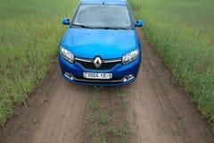 GOMEL, WEISSRUSSLAND - 24. Mai 2017: Blaues Auto RENO LOGANs wird auf dem grünen Feld geparkt Lizenzfreie Stockfotos