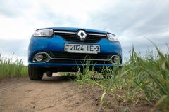 GOMEL, WEISSRUSSLAND - 24. Mai 2017: Blaues Auto RENO LOGANs wird auf dem grünen Feld geparkt Lizenzfreie Stockbilder