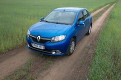 GOMEL, WEISSRUSSLAND - 24. Mai 2017: Blaues Auto RENO LOGANs wird auf dem grünen Feld geparkt Lizenzfreies Stockbild