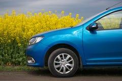 GOMEL, WEISSRUSSLAND - 24. Mai 2017: das blaue Auto wird auf dem Rapssamenfeld geparkt Stockfotos