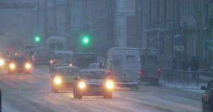 Gomel, Wit-Rusland Stadsverkeer op Sovetskaya-Straat in de Avondtijd van de de Winter Sneeuwsneeuwstorm stock video