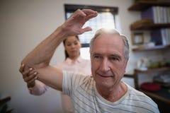 Gomito d'esame di medico femminile del paziente senior maschio fotografia stock libera da diritti