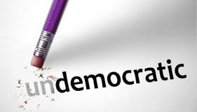 Gomma che cambia la parola antidemocratica per democratico immagini stock