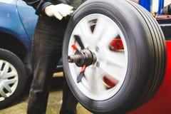 Gomma di automobile d'allineamento del meccanico a servizio Fotografie Stock Libere da Diritti