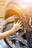 Gomma di automobile di lavaggio della mano con la spugna nera Fotografia Stock