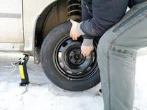 Gomma perforata e piana sulla strada Sostituendo la ruota con una presa dal driver immagini stock libere da diritti