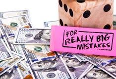 Gomma rosa con il messaggio per gli errori realmente grandi sopra cento banconote in dollari e dadi immagine stock