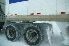 Gomme del camion che filano sulla strada principale durante la bufera di neve Fotografia Stock